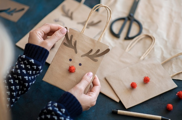 Hands holding adorable reindeer decorated christmas present bag
