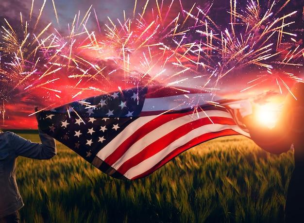 Руки держат американский флаг на закате с фейерверком 4 июля в день независимости