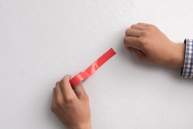 접착식 컬러 테이프를 손에 들고 흰색 표면에 바릅니다.