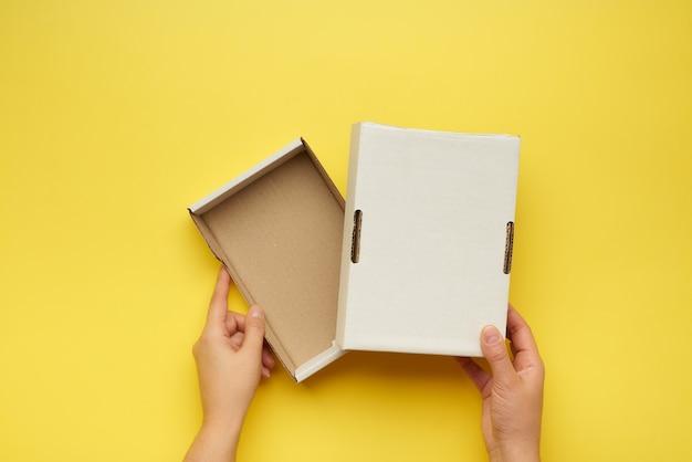 Руки держат открытую пустую коробку