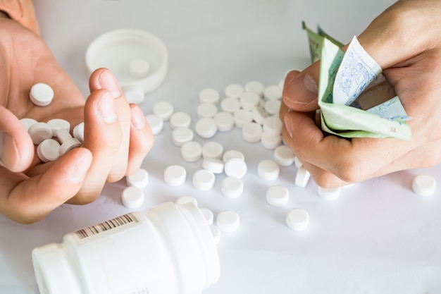 Hands holding analgesic medicine scattered