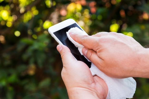 Руки держат и чистят сотовый телефон