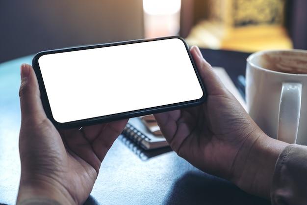 Руки держат и используют черный мобильный телефон с пустым экраном по горизонтали для просмотра с чашкой кофе и ноутбуками на столе