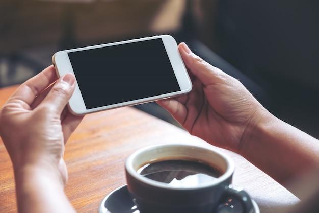 木製のテーブルの上にコーヒーカップで見るために水平に空白の黒い画面と白い携帯電話を保持して使用する手