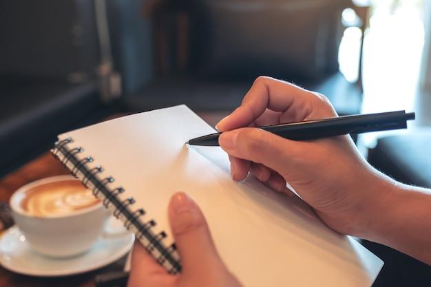 手を押しながらカフェで白い空白のノートブックに書き留めて