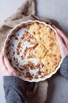 白いカビでリンゴのクランブルパイを保持している手