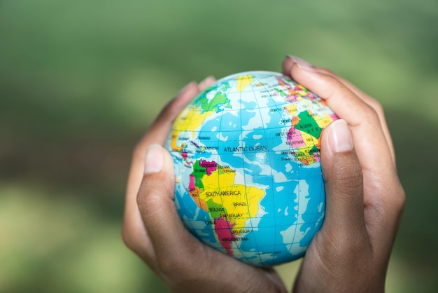 Hands holding ball globe in selective focus, elements of this image furnished by nasa.