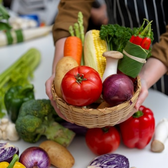 Hands holding basket of several fresh farm vegetables while standing at table with other fresh vegetables