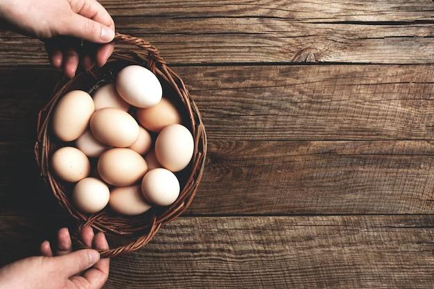 Руки держат корзину с куриными яйцами на деревянном фоне органических домашних хозяйств