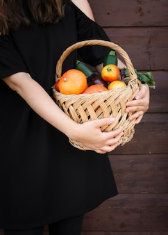 Hands holding basket with vegetables