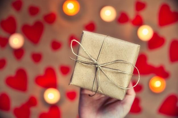 美しいギフトボックスを持っている手、ギフトを与える女性、バレンタインデー、上面図の背景