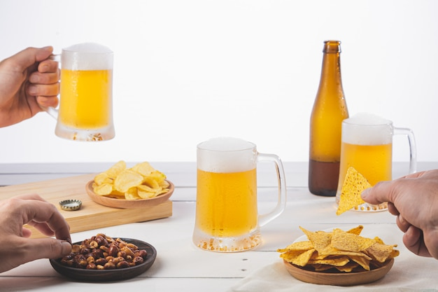 Hands holding beer and sharing a snack on white wooden base