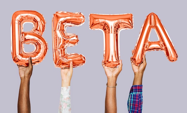 Hands holding beta word in balloon letters