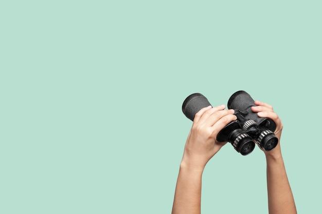Hands holding binoculars on green background