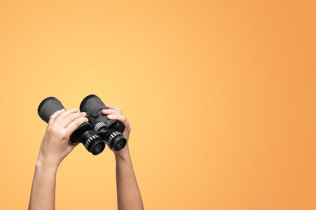 Hands holding binoculars on yellow background