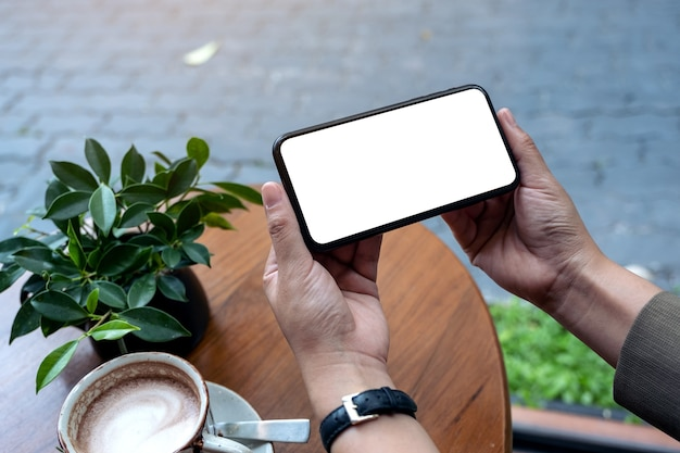 Hands holding black mobile phone with blank desktop screen horizontally in cafe