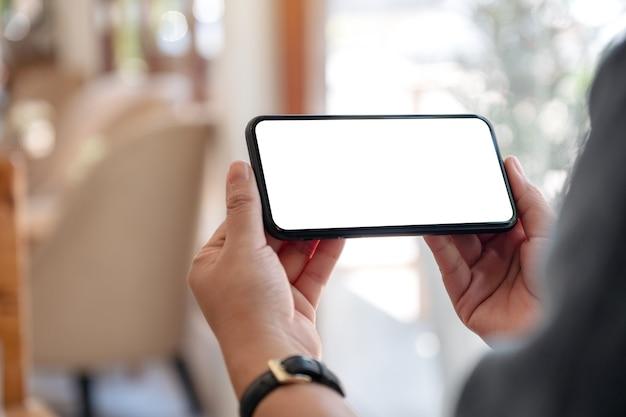 Руки держат черный мобильный телефон с пустым экраном рабочего стола по горизонтали в кафе