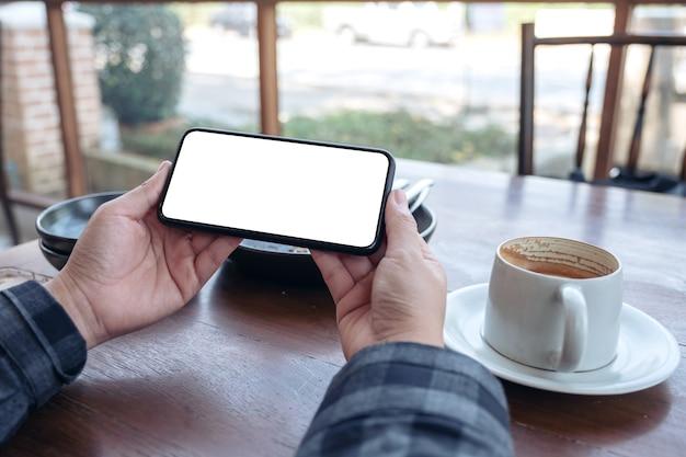 Руки держат черный мобильный телефон с пустым экраном рабочего стола по горизонтали с чашкой кофе на столе