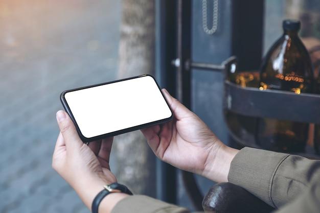 Руки держат черный мобильный телефон с пустым экраном рабочего стола по горизонтали