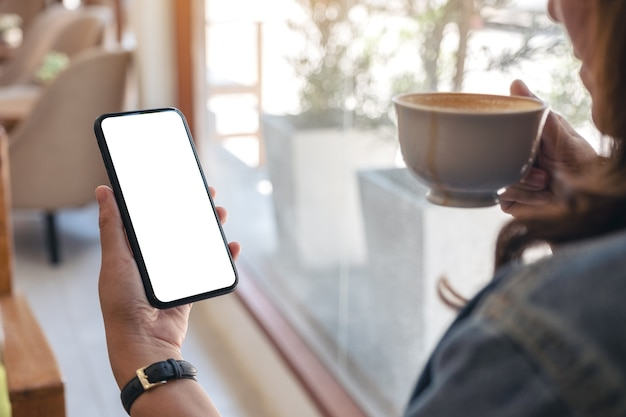 Hands holding black mobile phone with blank desktop screen while drinking coffee in cafe