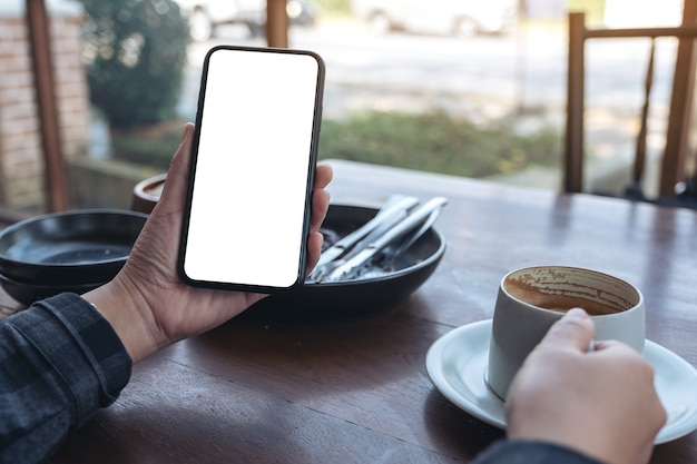 Hands holding black mobile phone with blank screen while drinking coffee in cafe
