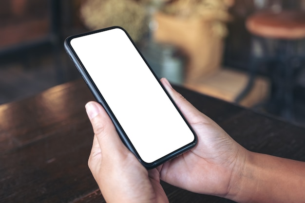 Руки, держащие черный мобильный телефон с пустым белым экраном в винтажном кафе