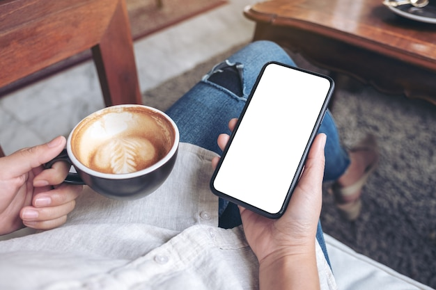Hands holding black mobile phone with blank white screen while drinking coffee