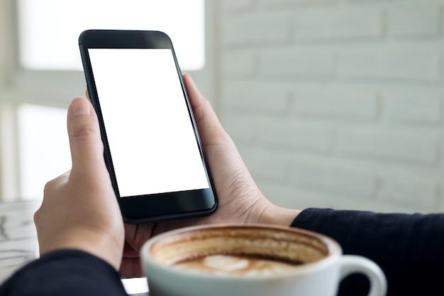카페에서 커피 한잔과 함께 빈 흰색 화면이 검은 휴대 전화를 들고 손