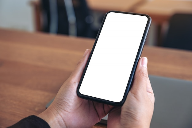 Hands holding black mobile phone with blank white screen with laptop on wooden table