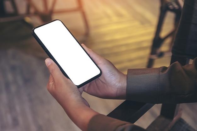 빈 흰색 화면으로 검은 휴대 전화를 들고 손