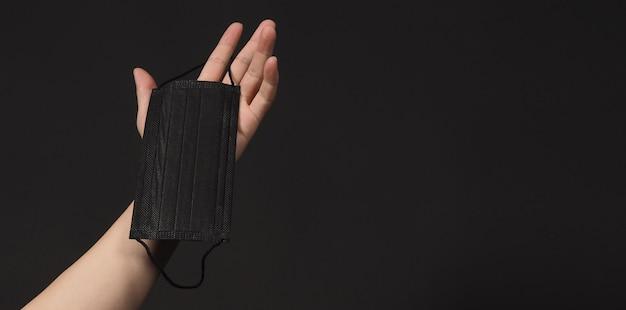 검은색 외과용 얼굴 마스크를 들고 있는 손입니다. 검은색 바탕에 의료용 마스크입니다.