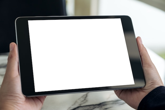 Hands holding black tablet pc with blank white desktop screen on table