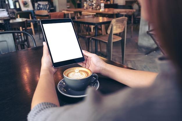 Руки держат черный планшетный пк с пустым белым экраном с чашкой кофе