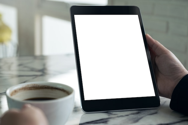 Руки, проведение черный планшетный пк с белым пустой экран и чашка кофе на фоне стола