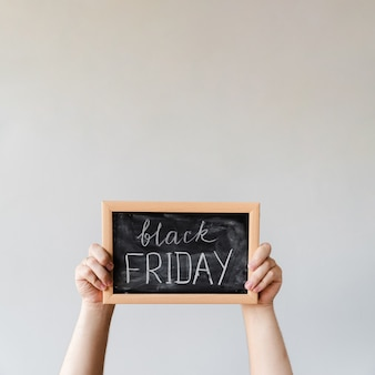 Hands holding blackboard with black friday text