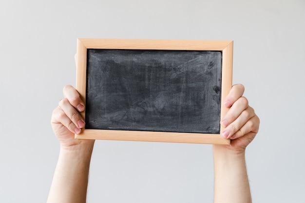 Hands holding blank blackboard