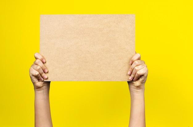 노란색 벽에 빈 갈색 종이 골 판지 보드 포스터를 들고 손