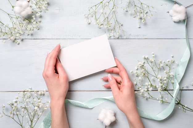Hands holding blank paper card on light blue wooden desk with flowers.