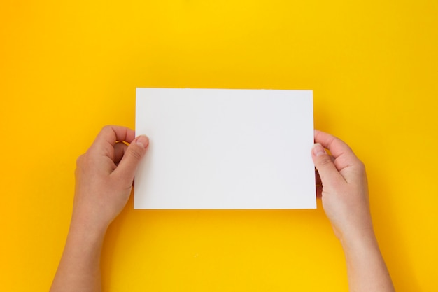 Hands holding blank white, empty paper isolated on yellow with copy space