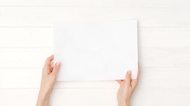 デザインのサイズの空白の白い紙を持つ手
