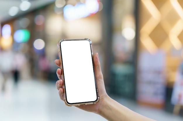 ぼやけているデパート、デジタル決済の概念で空白の画面の携帯電話を保持している手