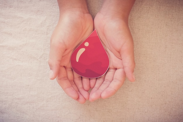 Hands holding blood drop,  give blood donation, blood transfusion, world blood donor day, world hemophilia day concept