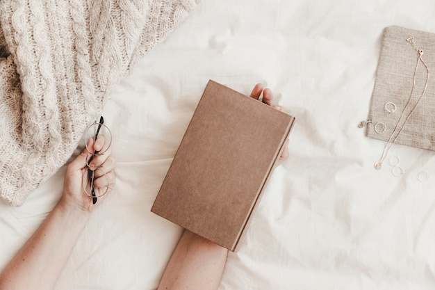 Hands holding book and eyeglasses on bed