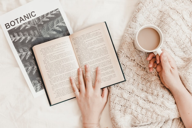 Hands holding book and hot drink lying on poster and plaid on bedsheet