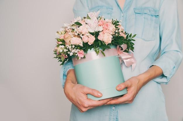 美しい花の花束を持っている手。トーンの写真