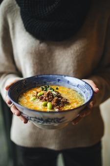 Hands holding a bowl of japanese ramen tantanmen
