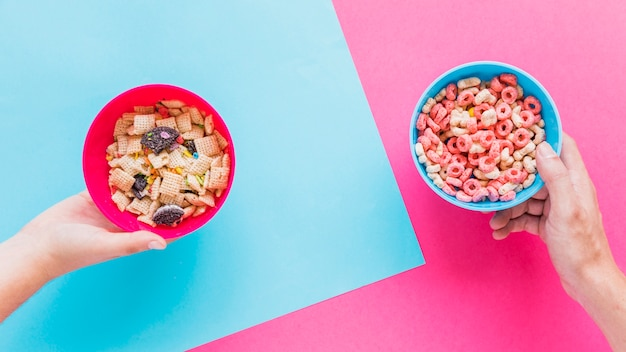Hands holding bowls with cereals