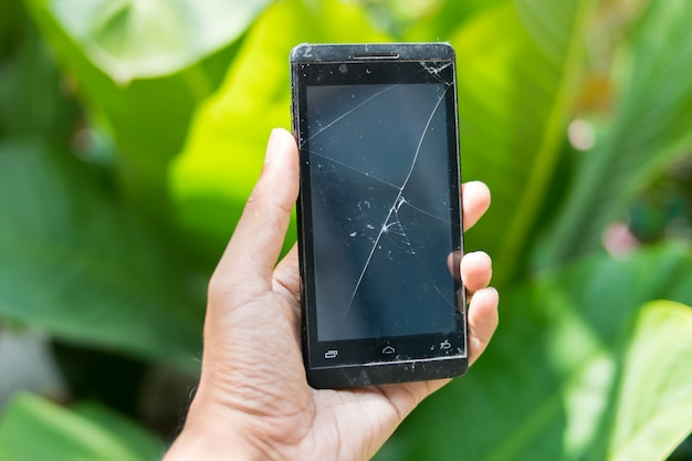 Hands holding broken mobile smartphone
