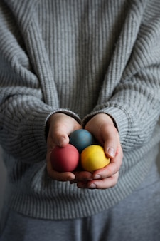 Hands holding bunch of colorful easter eggs