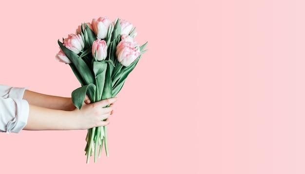 Руки, держа букет розовых тюльпанов на розовом фоне, женский день поздравительной открытки Premium Фотографии